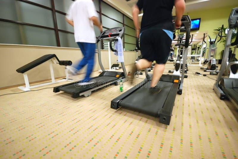 Man som kör på treadmillen i idrottshall fotografering för bildbyråer