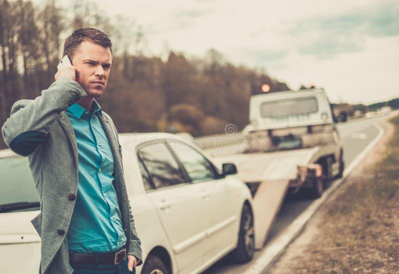 Man som kallar nära hans brutna bil royaltyfria foton