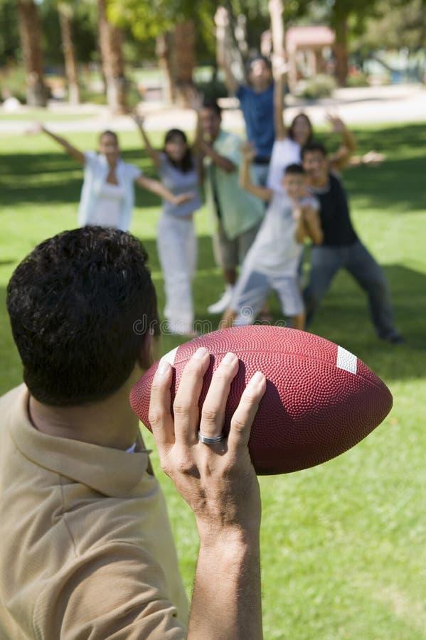Man som kastar fotboll till grupp människorbaksidasikten. arkivfoto
