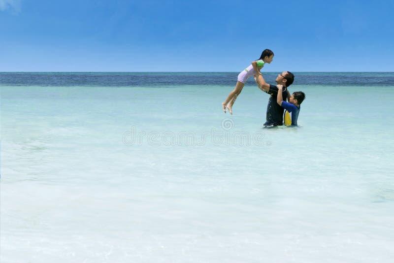 Man som kastar hennes dotter på stranden arkivfoto