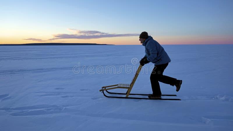 Man som kicksledding för att bli färdigt under vintermånader royaltyfri foto