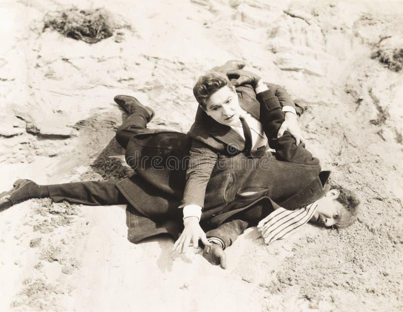 Man som klämmas fast till jordningen under kamp royaltyfria foton