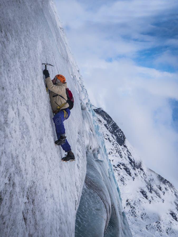 Man som klättrar den iskalla klippan eller glaciären i Island royaltyfria bilder