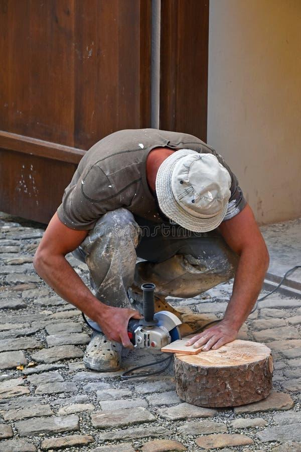 Man som klipper den keramiska tegelplattan med vinkelmolar royaltyfria bilder