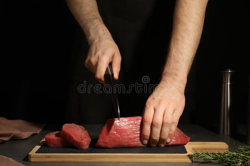 Man som klipper nytt rått kött på tabellen mot mörk bakgrund arkivbild