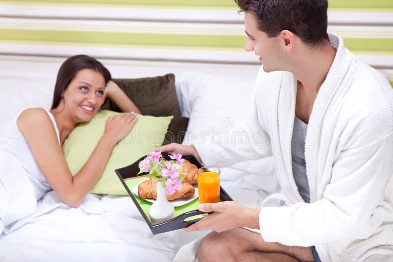 Man som kommer med frukosten i säng royaltyfria bilder
