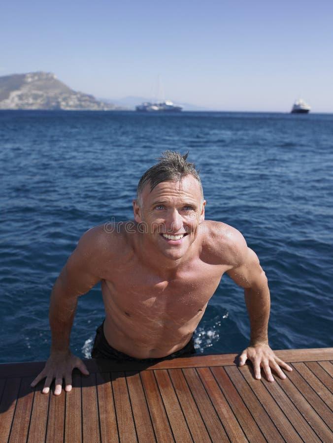 Man som kommer ut ur vatten på yachts golvtilja royaltyfri fotografi