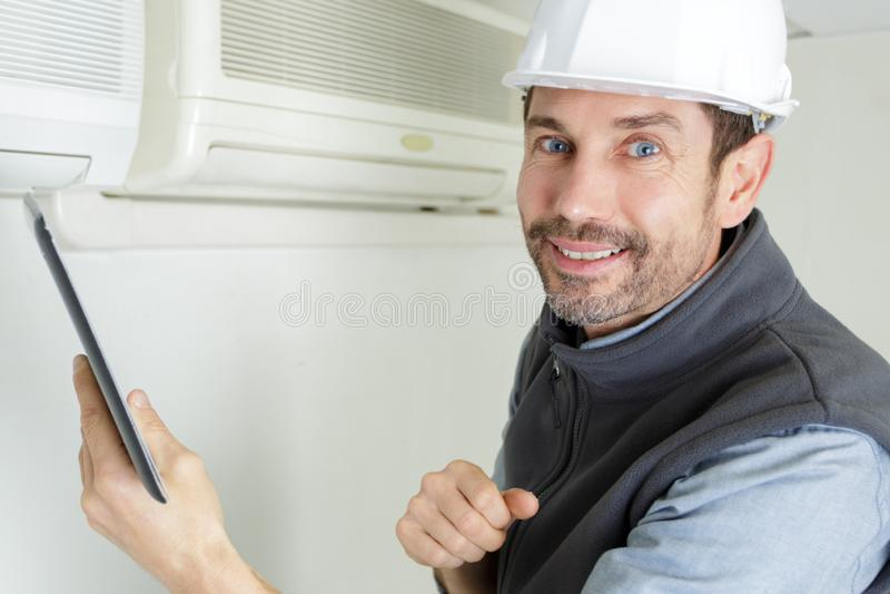 Man som kontrollerar airconditioning royaltyfri foto