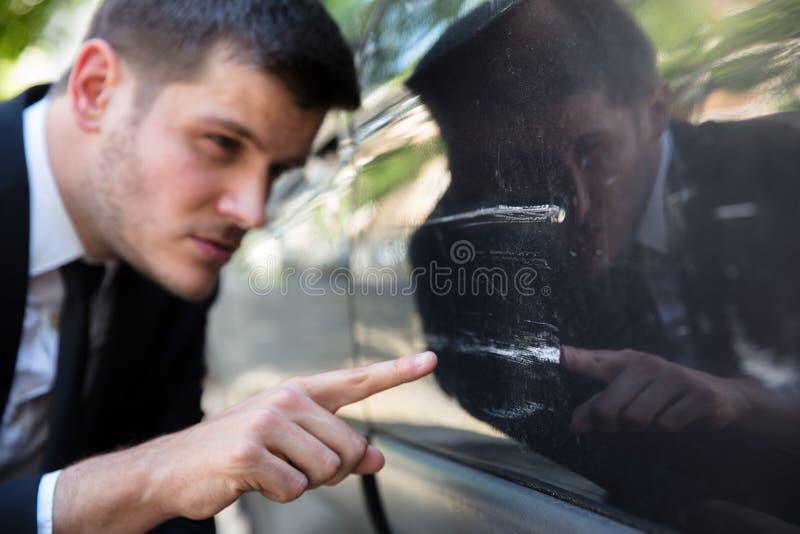 Man som kontrollerar den skadade bilen fotografering för bildbyråer