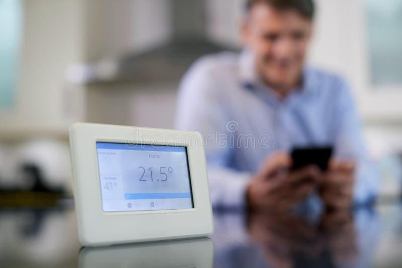 Man som kontrollerar den smarta metern för centralvärme genom att använda appen på mobil arkivbild