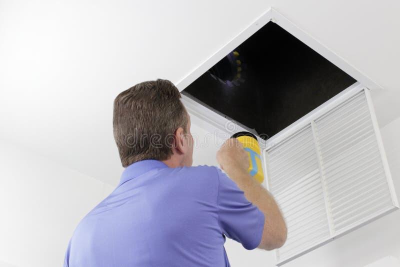 Man som kontrollerar en luftkanal med en ficklampa royaltyfria bilder