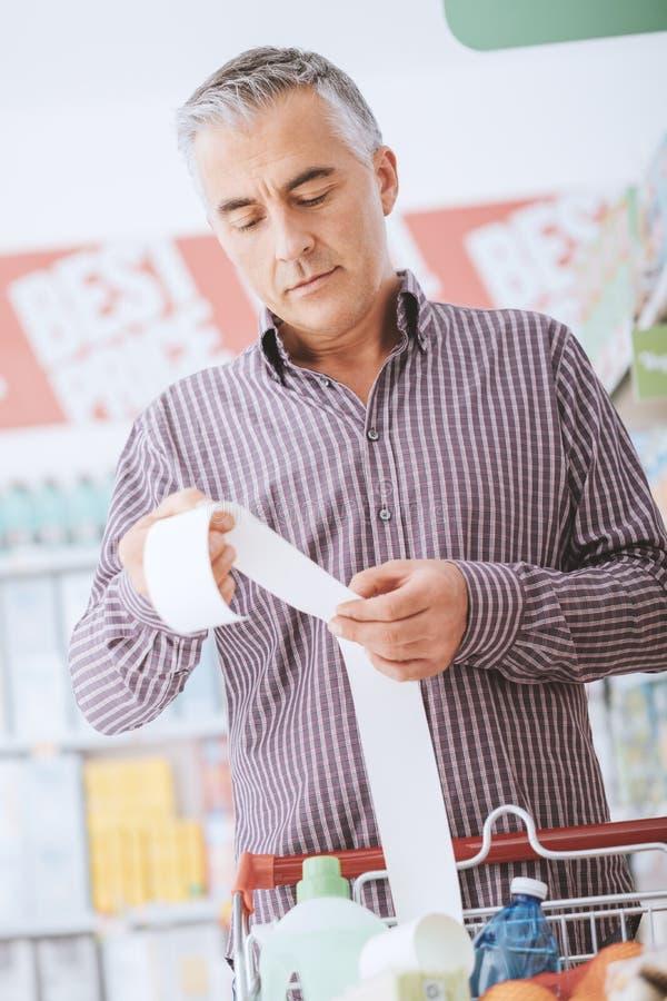 Man som kontrollerar ett livsmedelsbutikkvitto arkivfoto