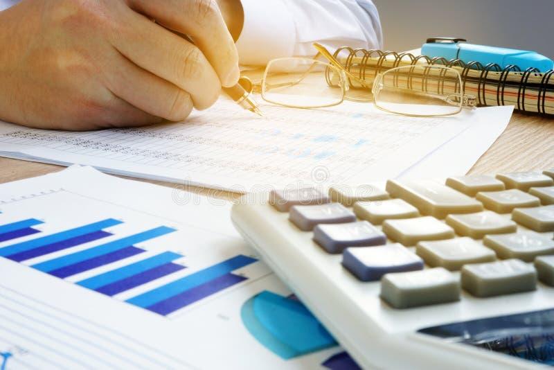 Man som kontrollerar finansiellt konto Affärsrevision arkivbild