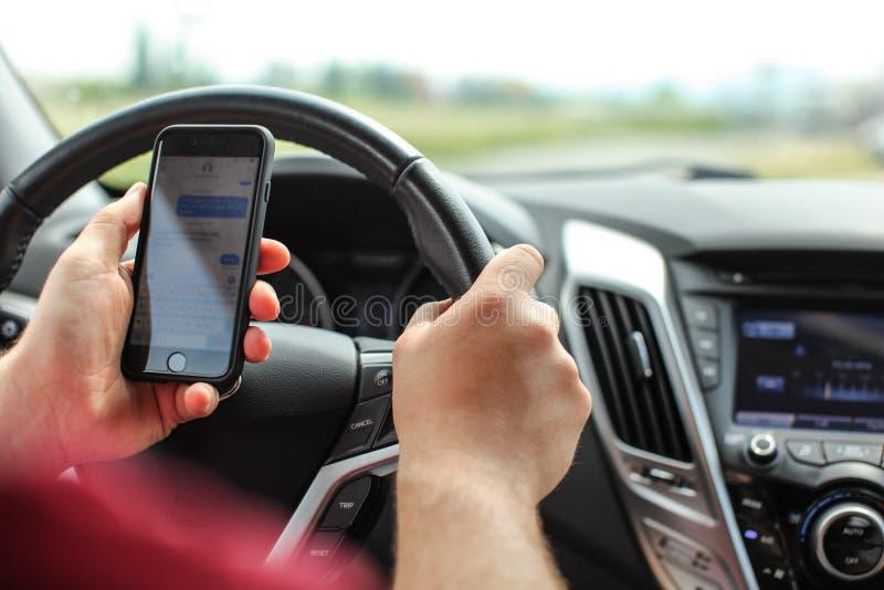 Man som kontrollerar hans textmeddelanden, medan köra Farligt smsa i bilbegrepp royaltyfria bilder