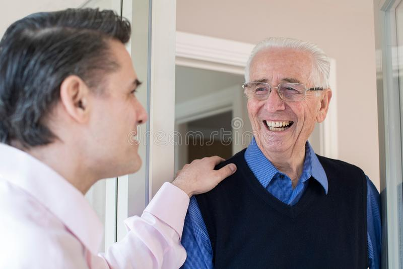 Man som kontrollerar på äldre manlig granne arkivfoto