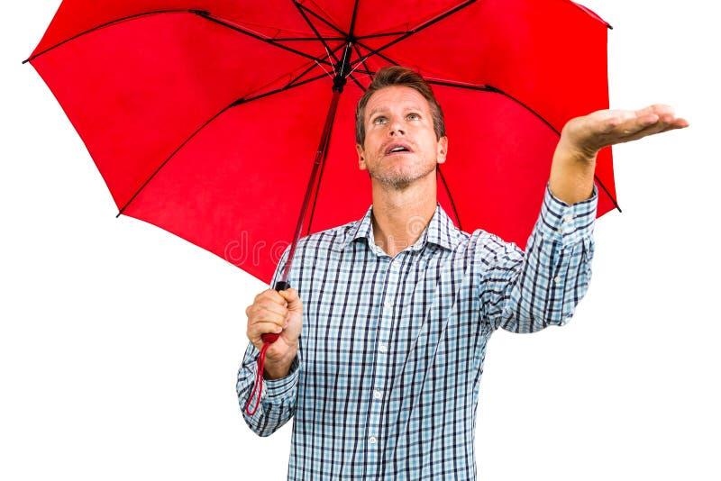 Man som kontrollerar väder, medan rymma det röda paraplyet royaltyfri foto