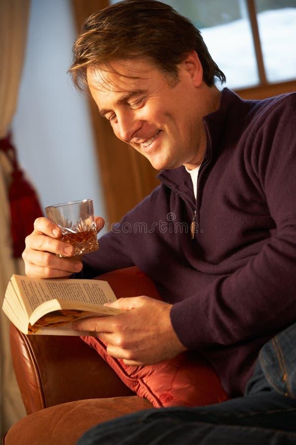 Man som kopplar av med boken som sitter på sofaen royaltyfri fotografi