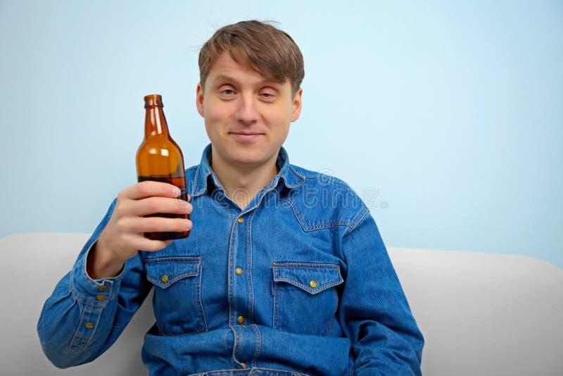 Man som kopplar av med en flaska av öl royaltyfri fotografi