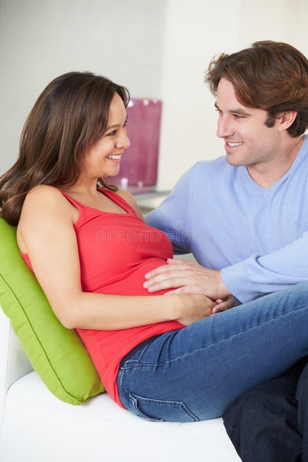 Man som kopplar av på det Sofa With Pregnant Wife At hemmet royaltyfria bilder