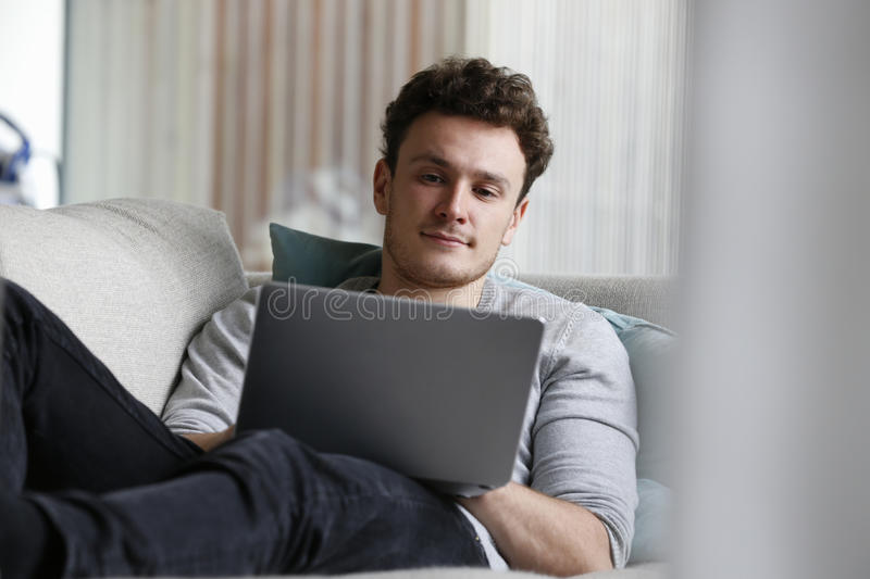 Man som kopplar av på Sofa Using Laptop Computer arkivbild
