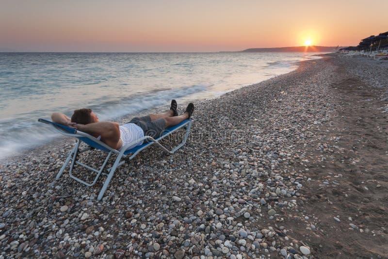 Man som kopplar av på stranden fotografering för bildbyråer