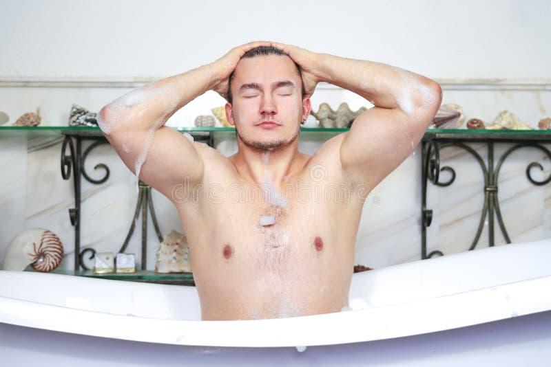 Man som kopplar av ta ett skummande bad Tvättar skum från huvudet Sexualitet- och avkopplingbegrepp Grabb i badrum med toalettart royaltyfria foton