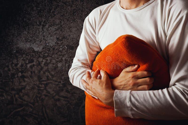 Man som kramar den orange kudden fotografering för bildbyråer