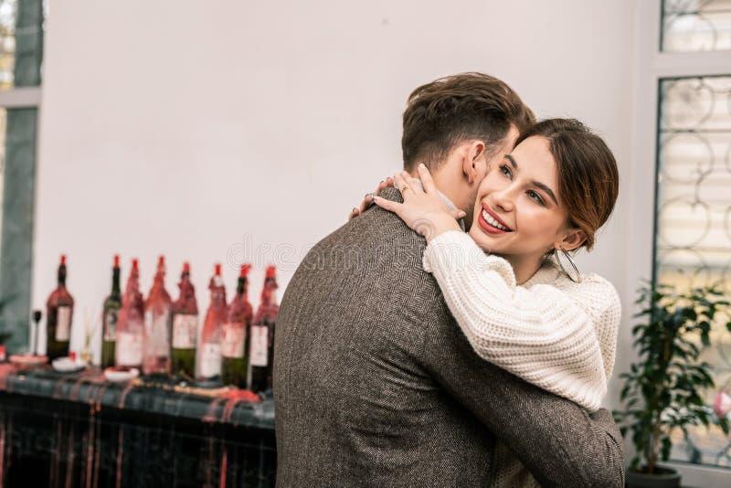 Man som kramar hans le flickvän i den romantiska atmosfären arkivbild