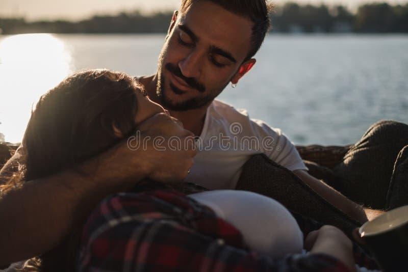 Man som kramar och ser hans flickvän vid floden royaltyfria foton