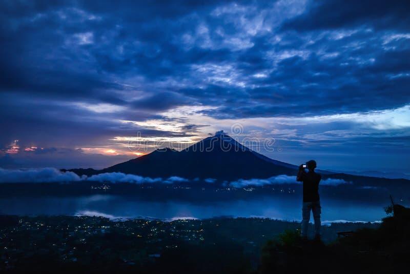 Man som kryssar bilden av den Agung vulkan fotografering för bildbyråer