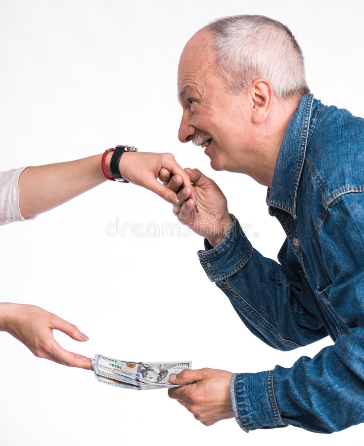 Man som kysser en woman& x27; s-hand och ge dollarräkningar arkivfoto