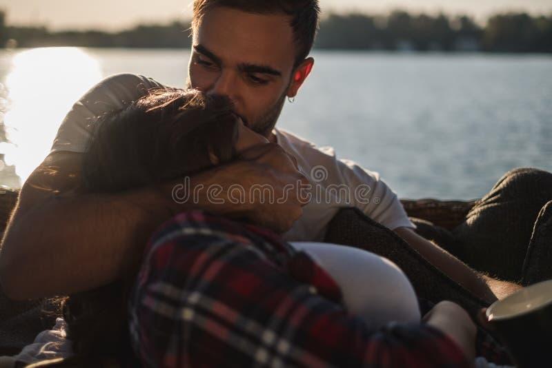 Man som kysser och kramar hans flickvän vid floden arkivfoto