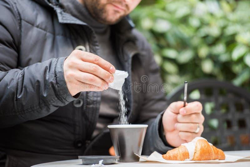 Man som läppjar socker i hans kaffe i en caffè/bar - nära övre arkivfoto