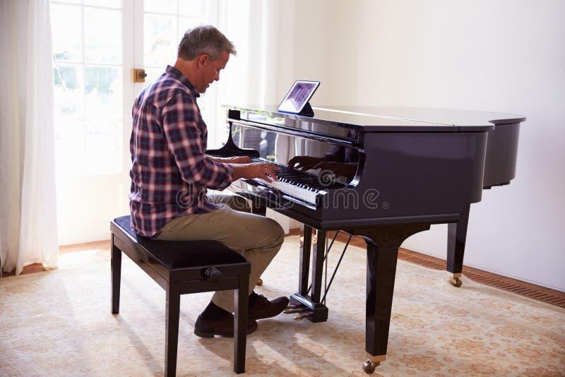 Man som lär att spela pianot genom att använda Digital minnestavlaapplikation arkivfoto
