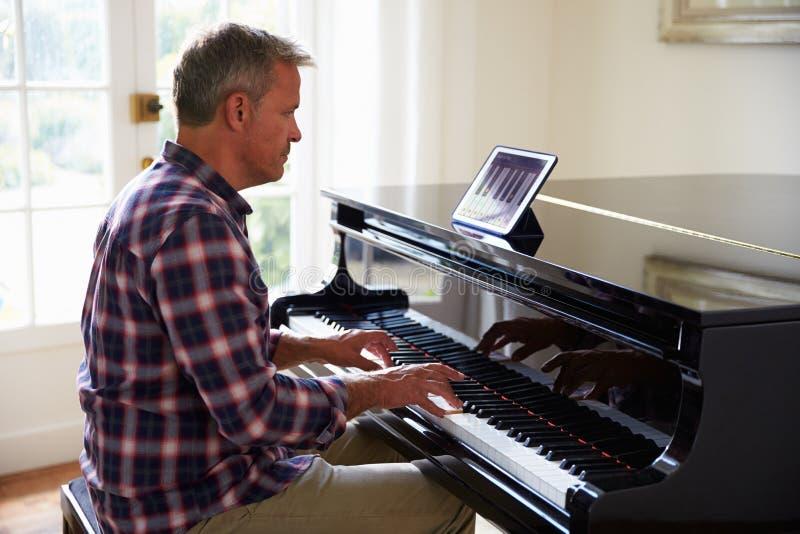 Man som lär att spela pianot genom att använda Digital minnestavlaapplikation fotografering för bildbyråer