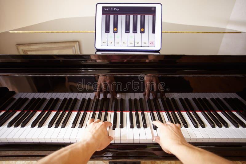Man som lär att spela pianot genom att använda Digital minnestavlaapplikation arkivfoton