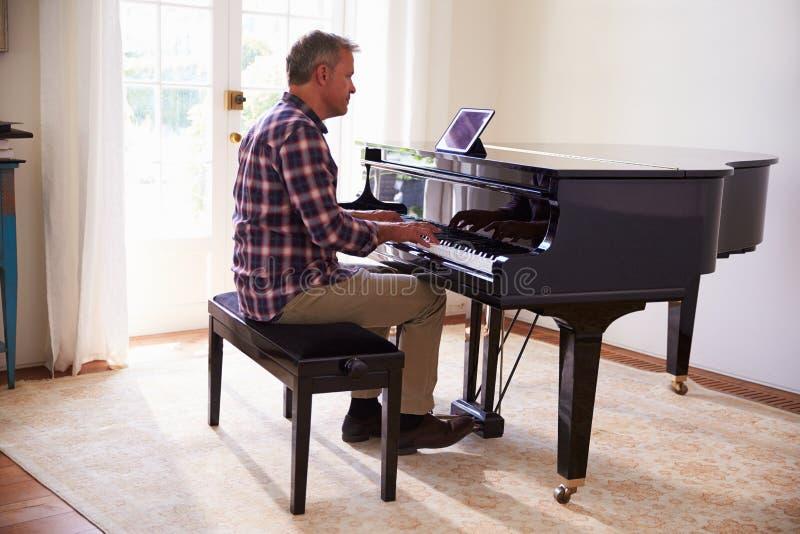 Man som lär att spela pianot genom att använda Digital minnestavlaapplikation royaltyfri fotografi