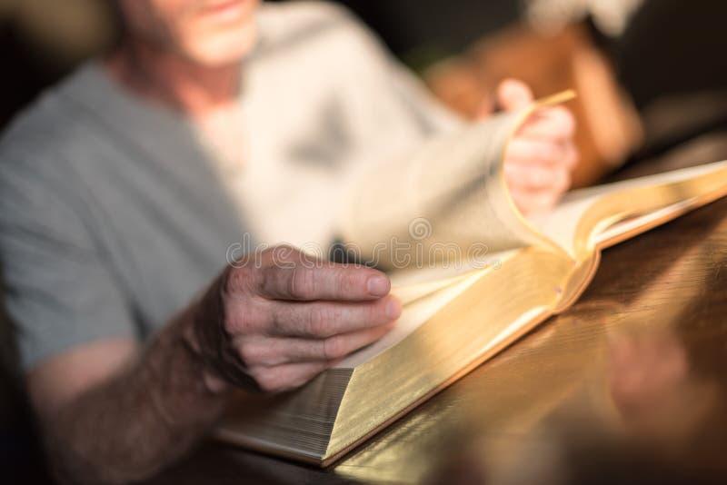 Man som läser bibeln arkivfoton