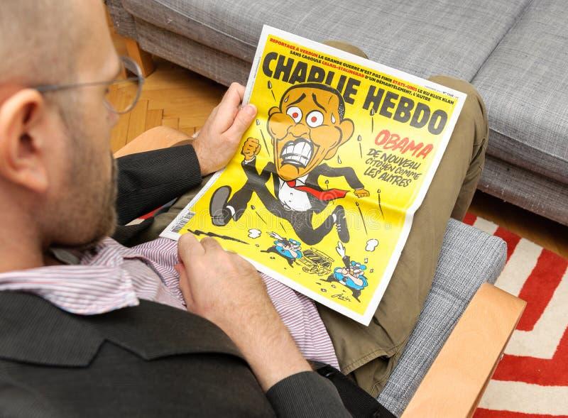 Man som läser Charlie Hebdo - Barack Obama Running från tjänstemän arkivfoton