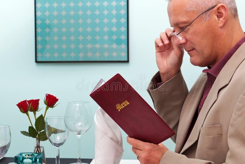 Man som läser en meny i en restaurang royaltyfria bilder
