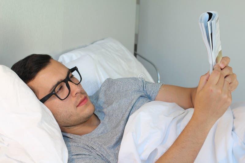 Man som läser en tidskrift i säng royaltyfria bilder