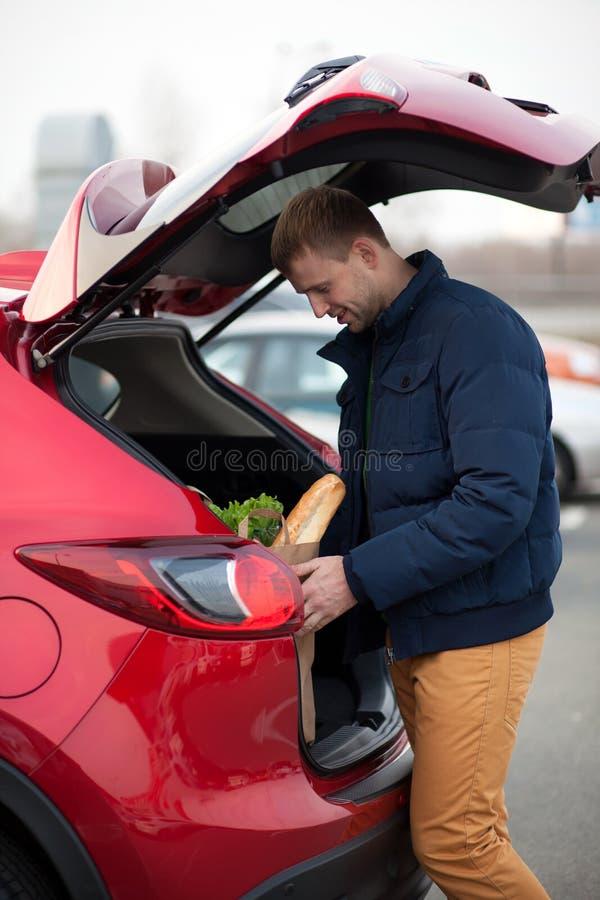 Man som laddar en shoppingpåse i bil arkivfoto
