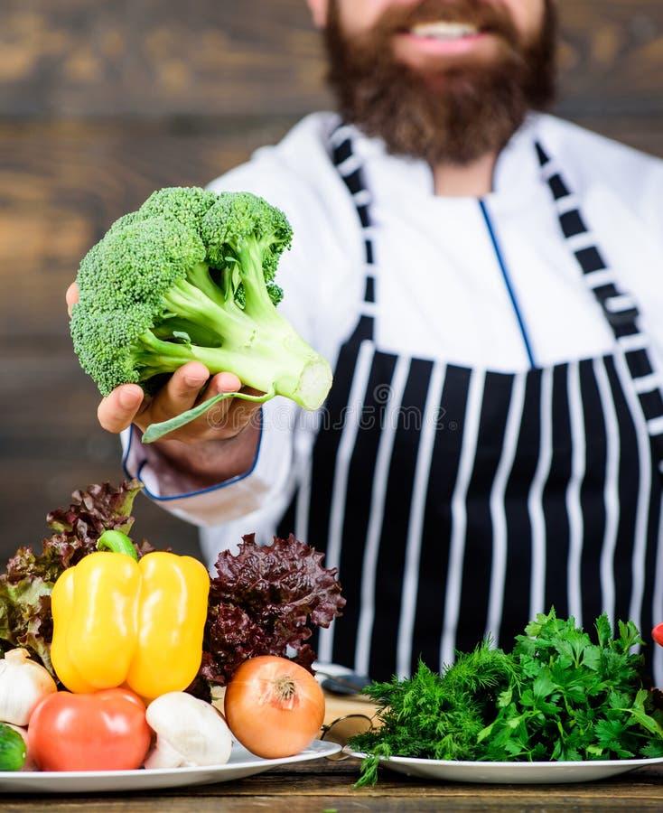 Man som lagar mat nya grönsaker Kulinariskt receptbegrepp Kocken använder nya organiska grönsaker för maträtt Laga mat för första royaltyfri bild