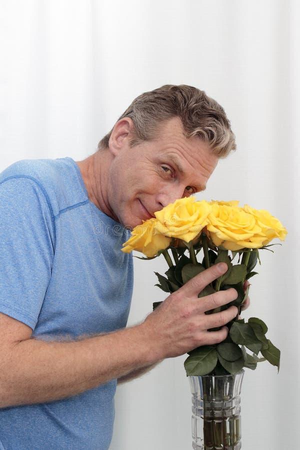 Man som ler håll och buketten för gula rosor för lukter royaltyfri foto