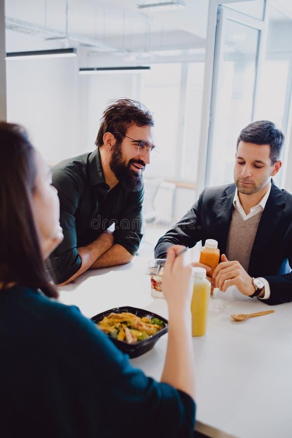 Man som ler i kontorskafeterian medan äta för kollegor royaltyfria bilder