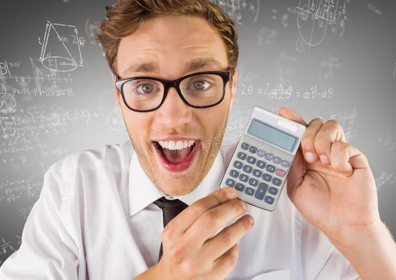 Man som ler med räknemaskinen mot vita matematikklotter och grå bakgrund royaltyfri bild