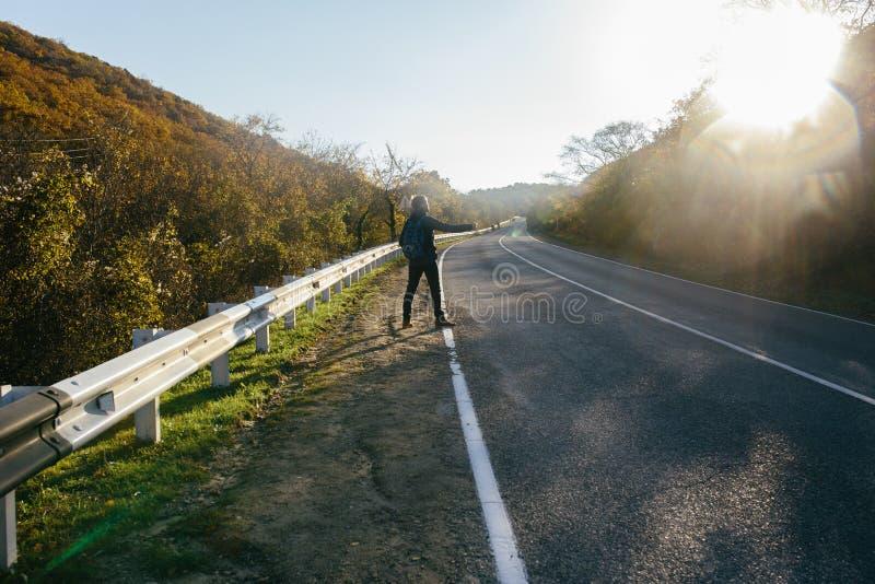 Man som liftar på en landsväg Handelsresandevisningtumme upp på för att lifta under vägtur arkivbilder