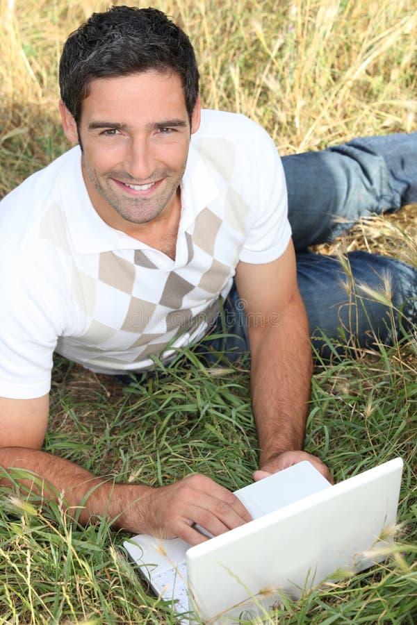 Man som ligger i gräset arkivbild