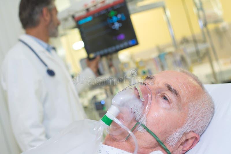 Man som ligger i sjukhussäng som får syre i intensiv-omsorg-enhet royaltyfria foton