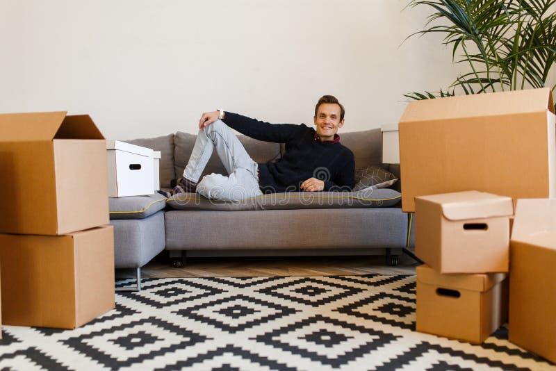 Man som ligger på den gråa soffan mot bakgrund av kartonger royaltyfri foto